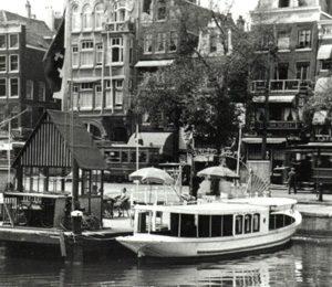 De Hilda aan het Damraksteigertje, vlak naast de Beurs van Berlage. Op de achtergrond de Amsterdamse panden aan het Damrak, met daarvoor een Amsterdamse tram uit 1930.